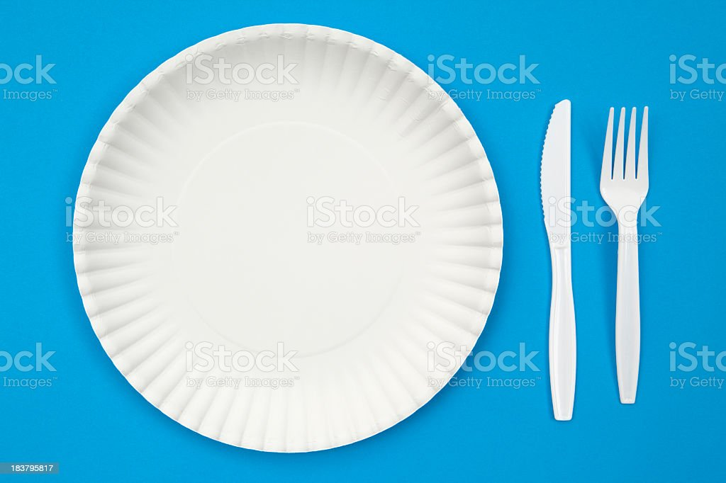 Paper plate and plastic utensils on blue background stock photo