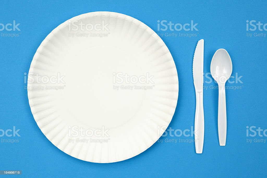 A paper plate next to plastic utensils on a blue table stock photo