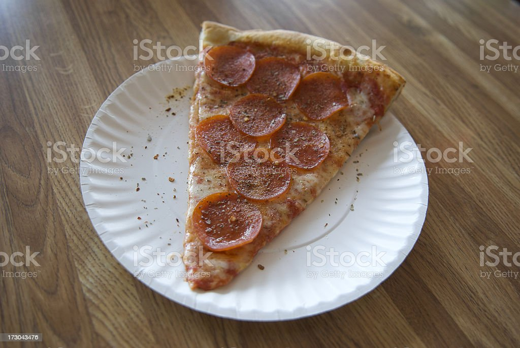 Paper Plate Pepperoni Pizza on Formica Table stock photo