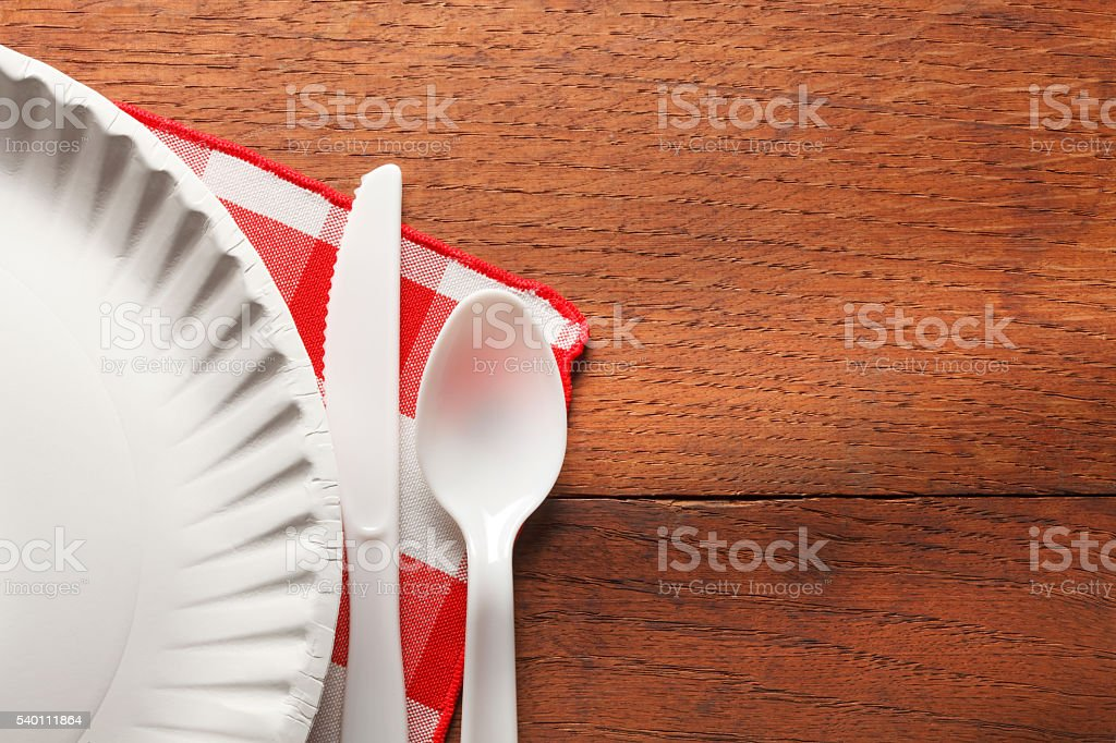 Paper Plate, Plastic Utensils And A Tablecloth On Picnic Tabel stock photo