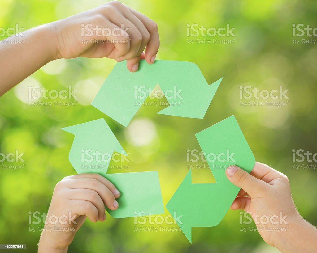 Paper RECYCLE sign in children`s hands stock photo
