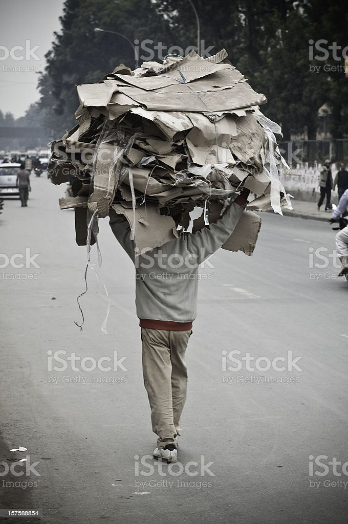 Paper recyling collector carrying heavy load down street Kathmandu Nepal royalty-free stock photo