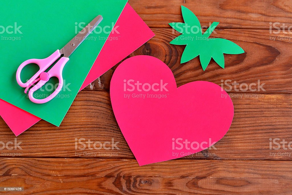 Paper red heart, paper green leaves on wooden table stock photo