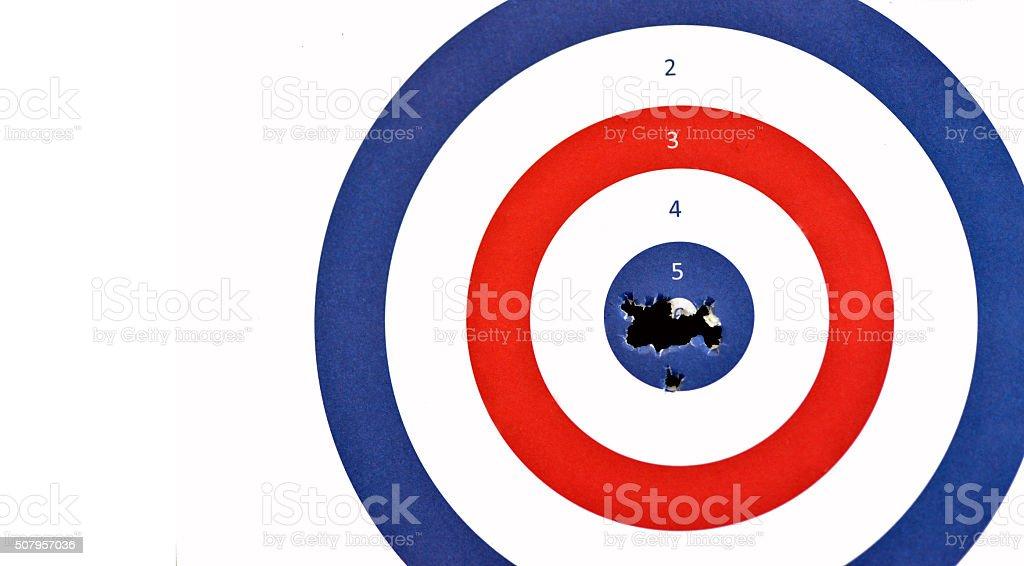 Paper Rifle target shot through the bullseye. stock photo