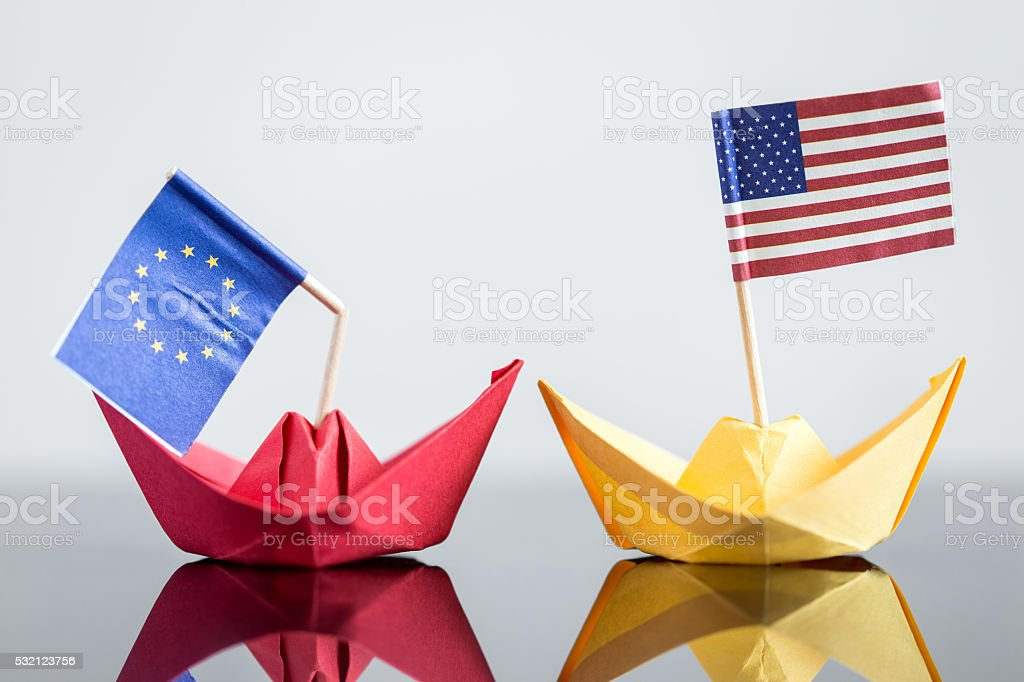 paper ship with usa and european flag stock photo