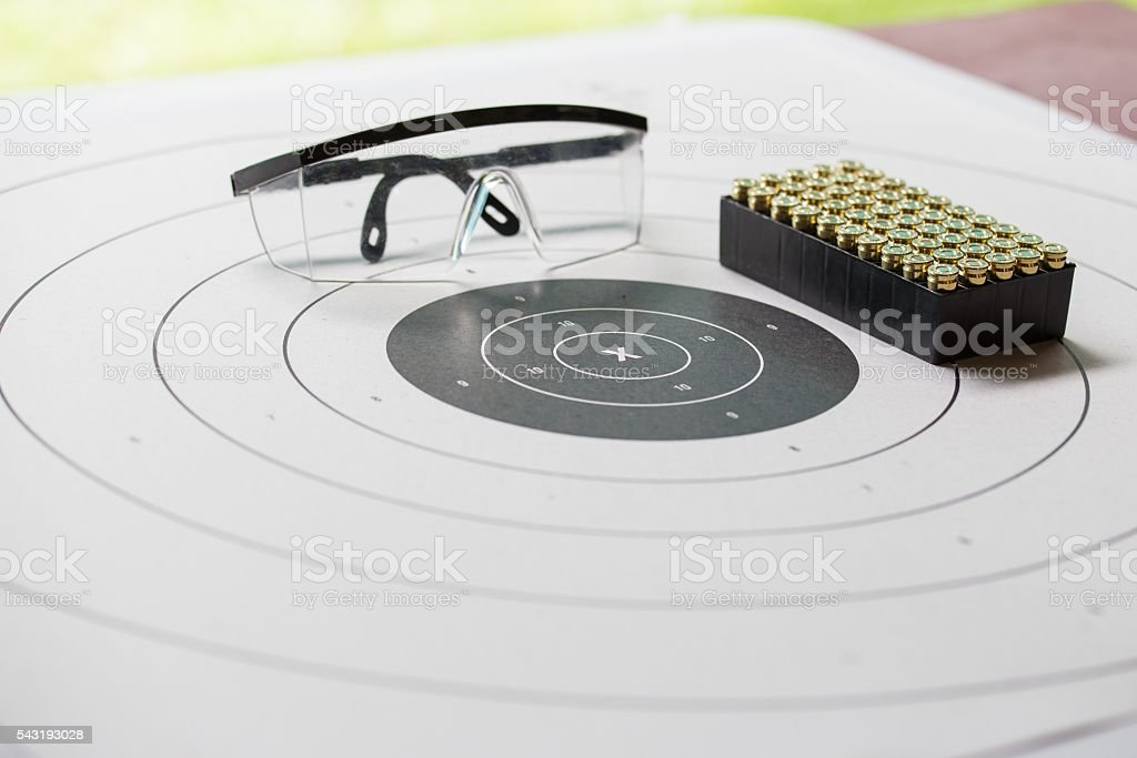 paper shooting target with safety glasses and 9 mm bullet stock photo