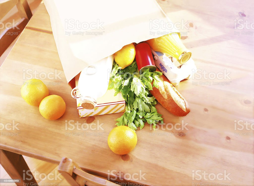Paper shopping bag full of healthy food on a wooden table stock photo