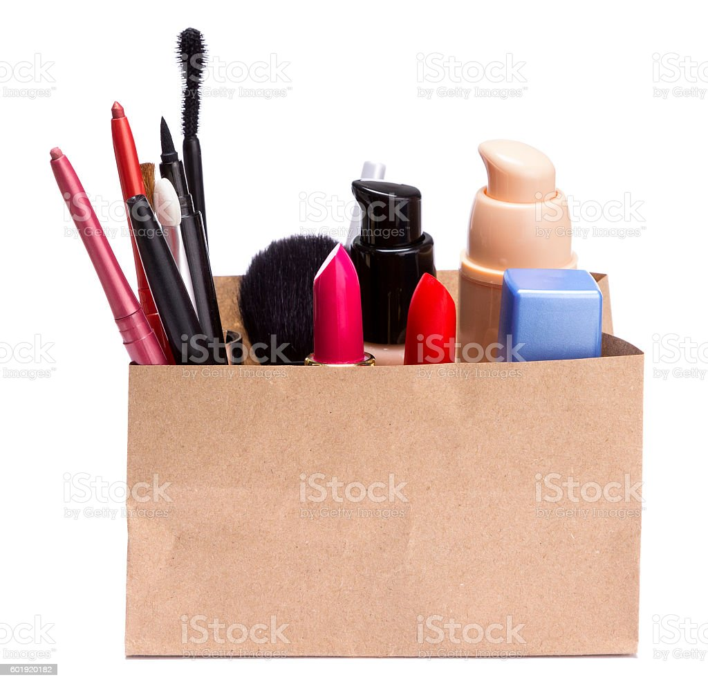 Paper shopping bag full of makeup cosmetics and accessories stock photo