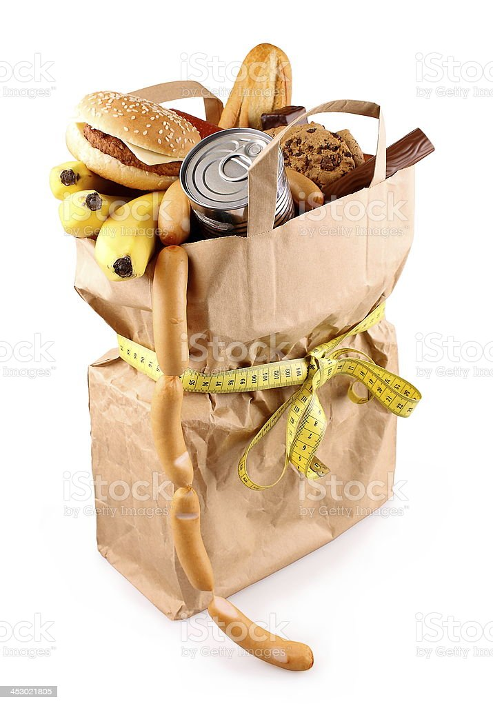 Paper shopping bag with high-calorie foods and measuring tape isolated royalty-free stock photo