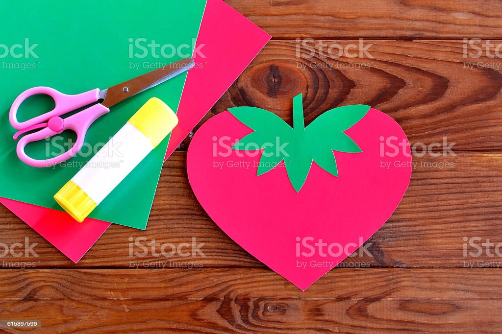 Paper strawberry, paper sheets, scissors, glue stock photo