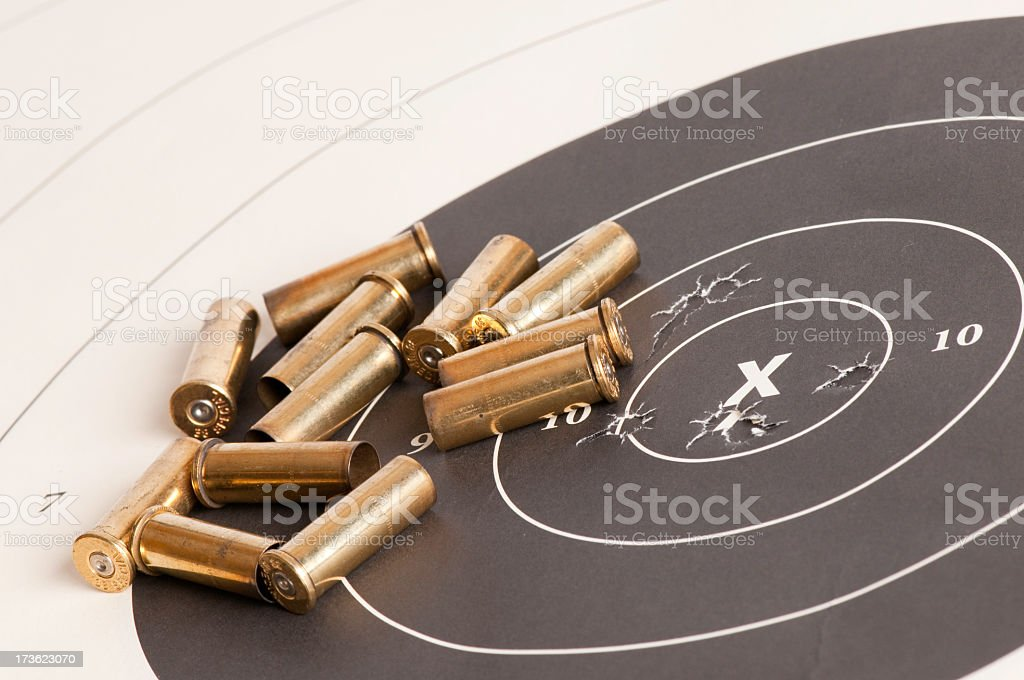 Paper target with gold bullets scattered on top stock photo