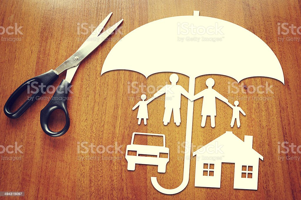 Paper umbrella sheltering paper family and home stock photo