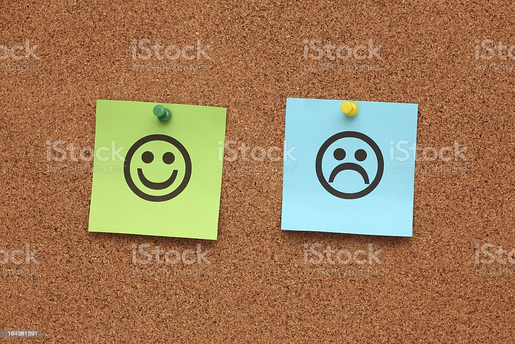 Paper with happy and sad faces on corkboard stock photo