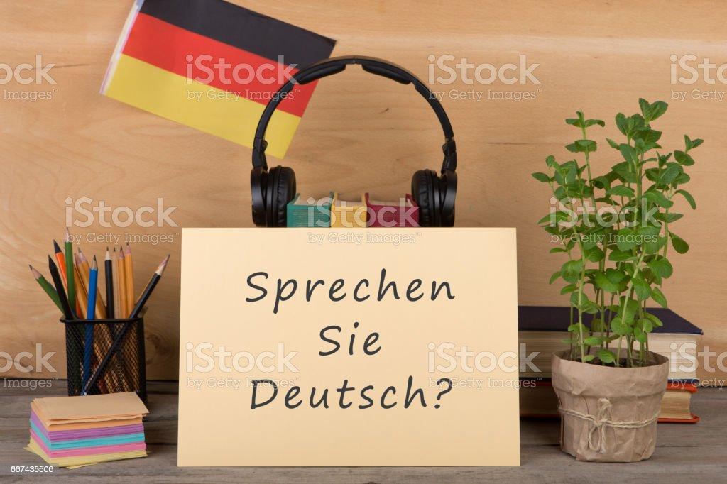 paper with text 'sprechen sie deutsch?', flag of the Germany stock photo