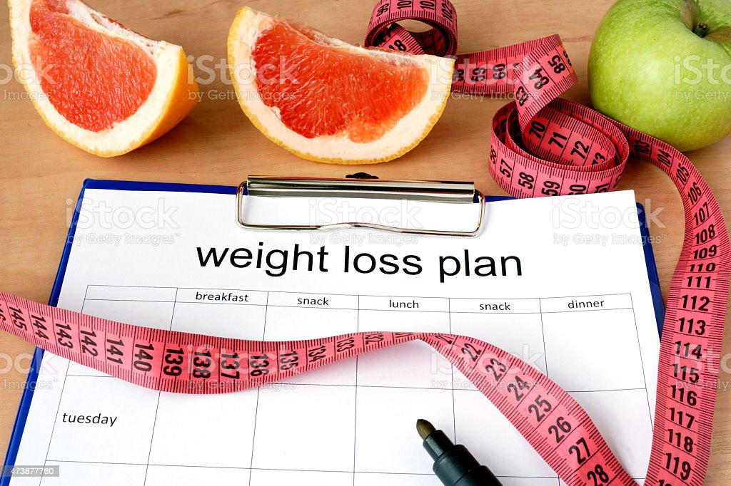 Paper with weight loss plan and grapefruit stock photo
