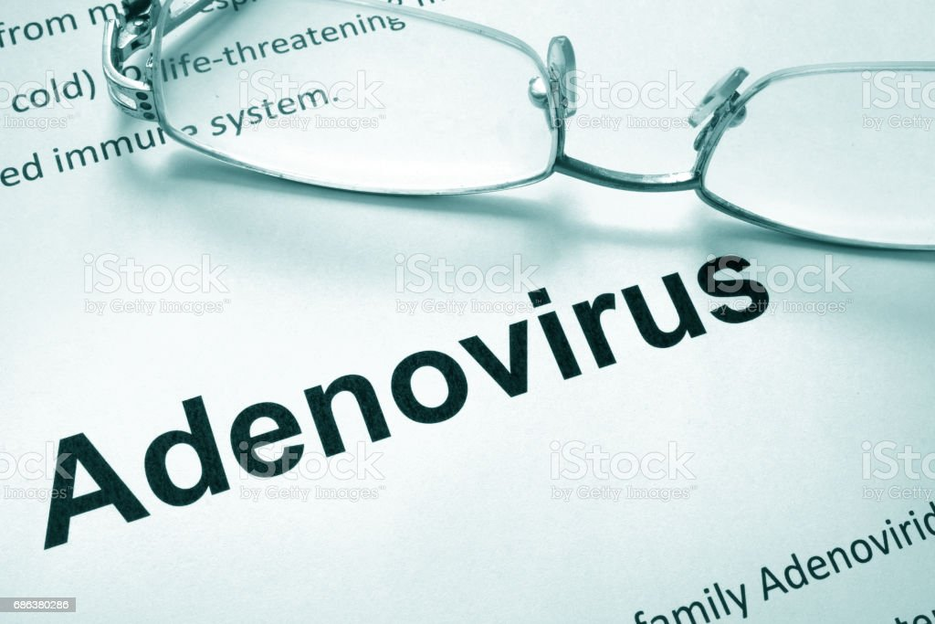 Paper with word adenovirus and glasses. Medical concept. stock photo