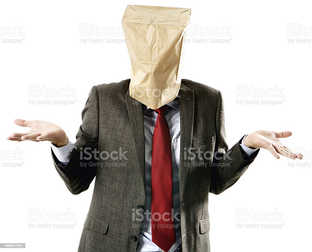 Paper-bag masked businessman shrugs, confused or unknowing stock photo