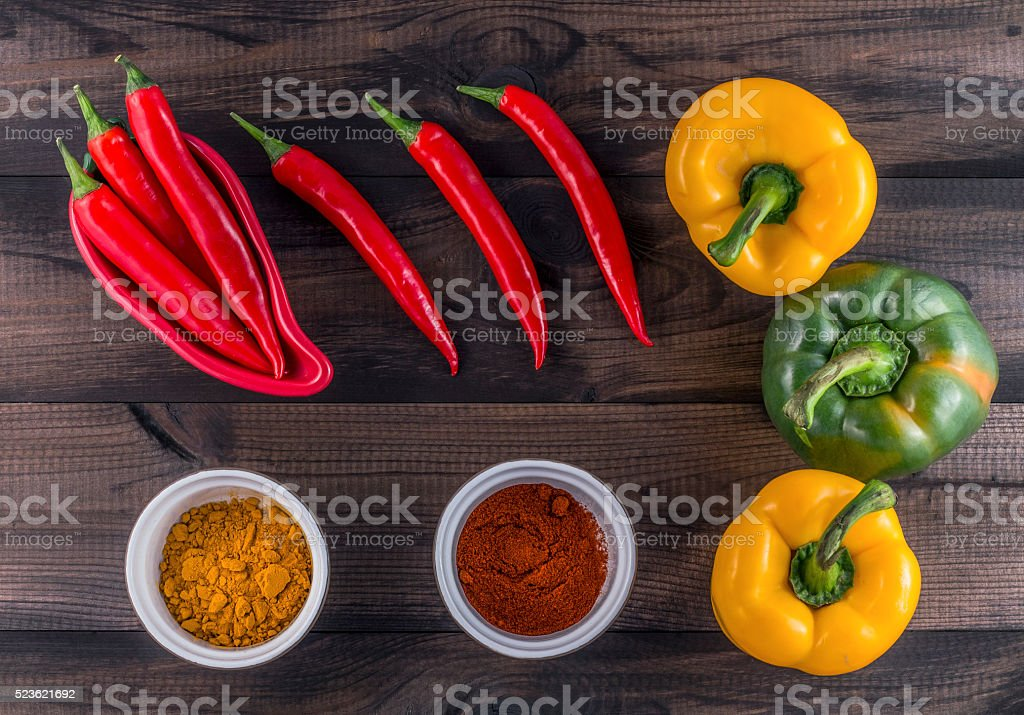 paprika, chilli peppers and chili powder on wooden table stock photo
