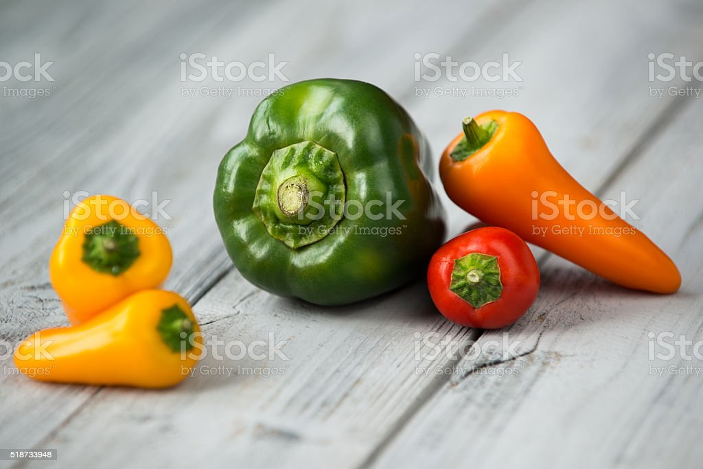 Paprika mix, mini peppers, green pepper on a wooden background stock photo