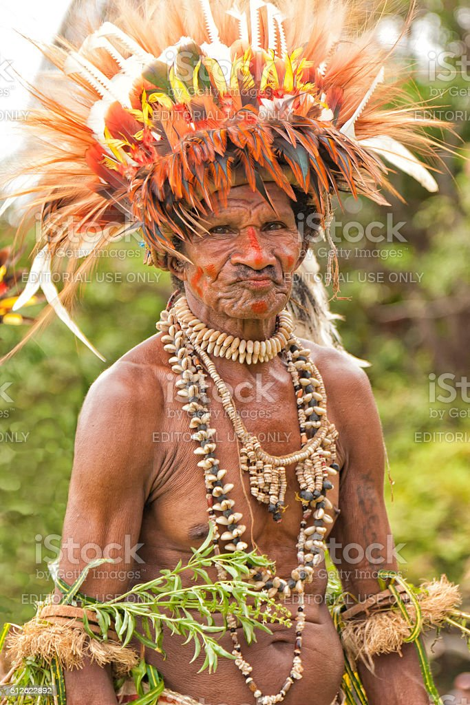 Papuan tribal man wearing colorful feathers in PNG village stock photo