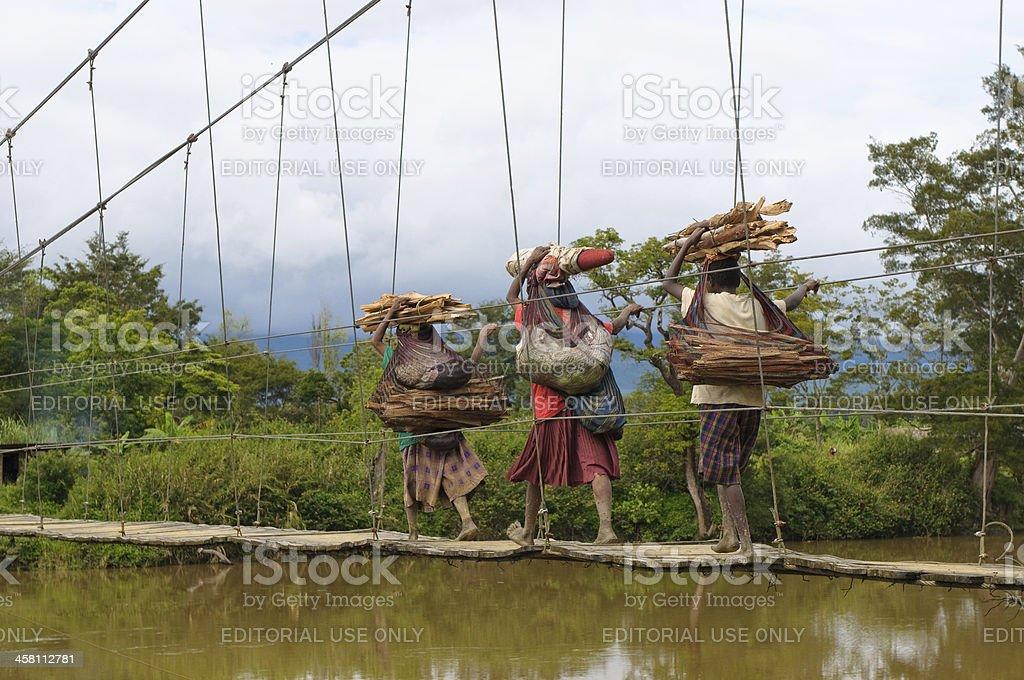 Papuan women crossing bridge, Wamena, Papua, Indonesia stock photo