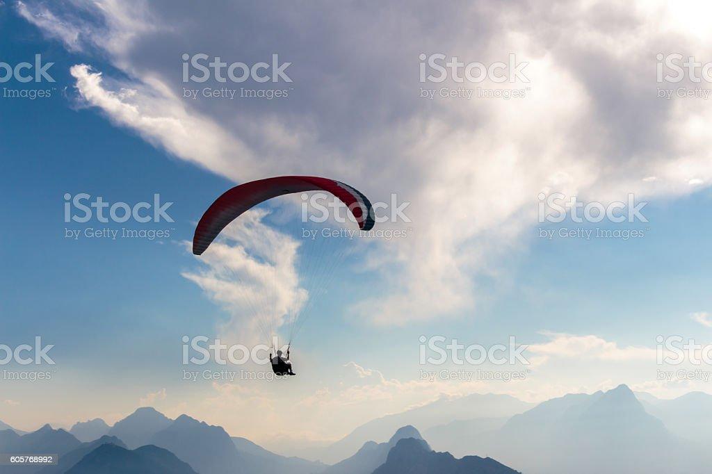 Parachute and human silhouette. Blu sky adventure. stock photo