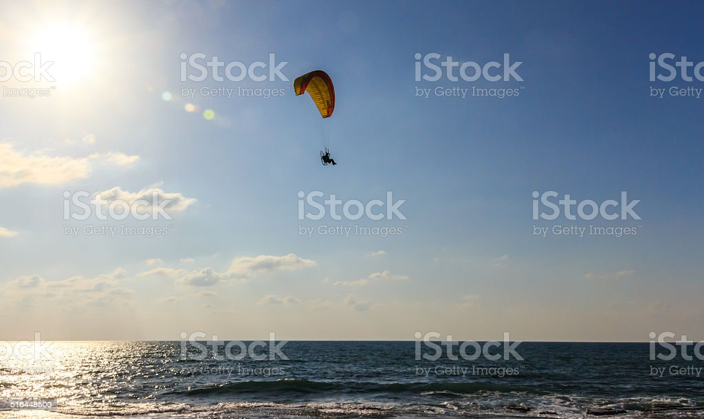 parachute jumper on motorized parachute flying over the sea stock photo