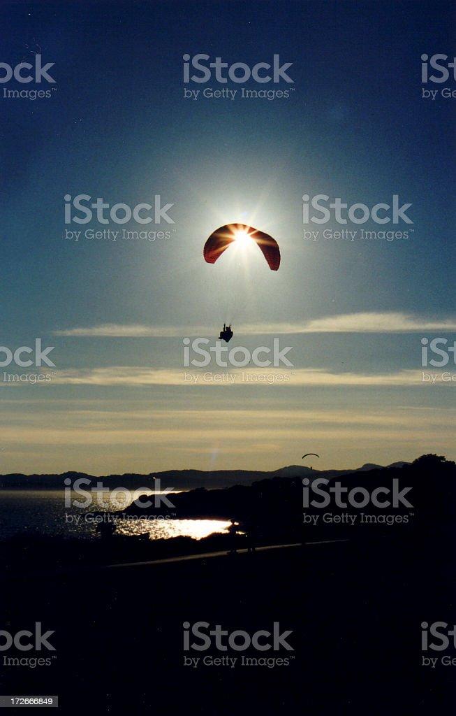Parachuter caught in the sunset stock photo