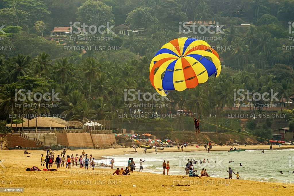 parachuter gliding over a populated beach stock photo