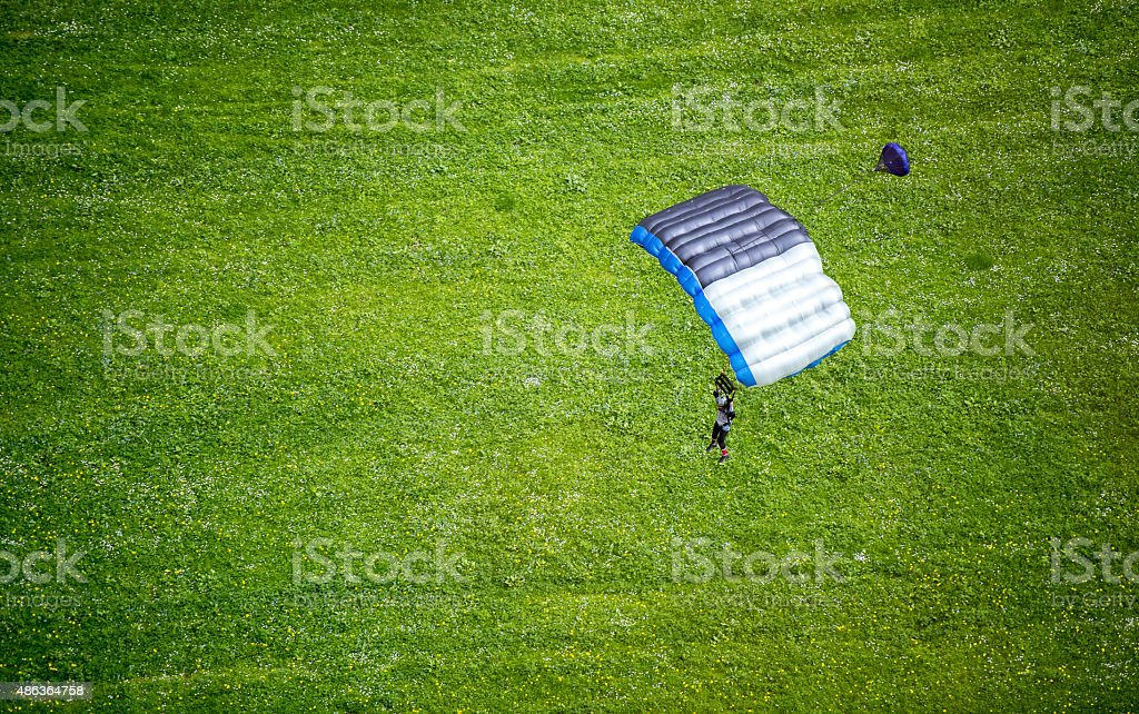 Parachuter sets down in mountain meadow stock photo