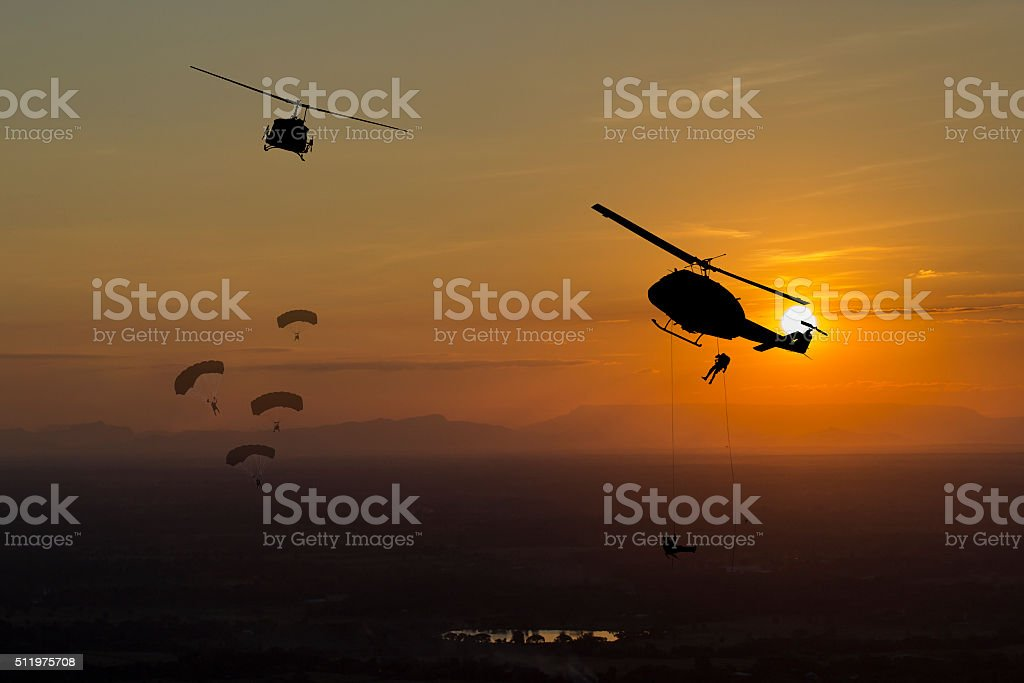 Parachuting exit from a helicopter at sunset stock photo