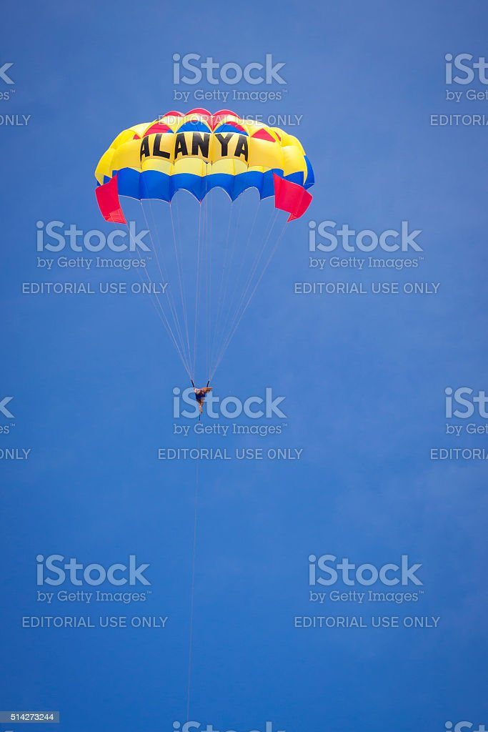 Parachutist in air wing's flying over black sea stock photo