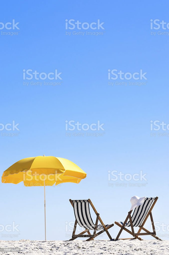 Paradise at the beach with folding chairs and an umbrella stock photo