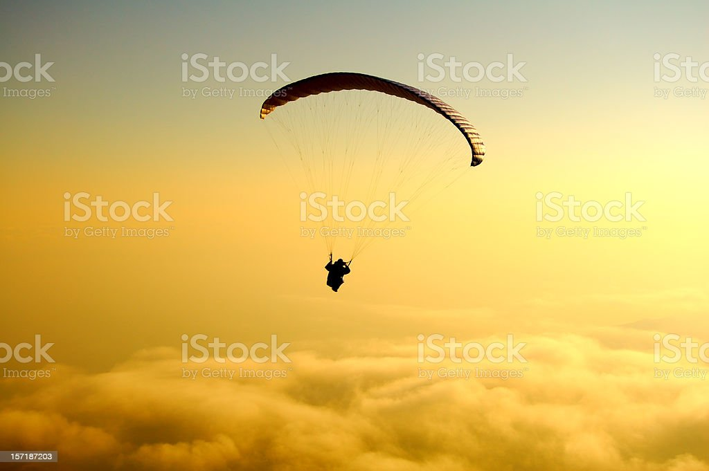 paraglide above yellow clouds on sunset royalty-free stock photo