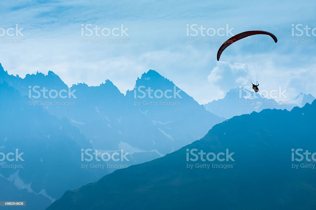Paraglide shadow figure over Alps peaks stock photo