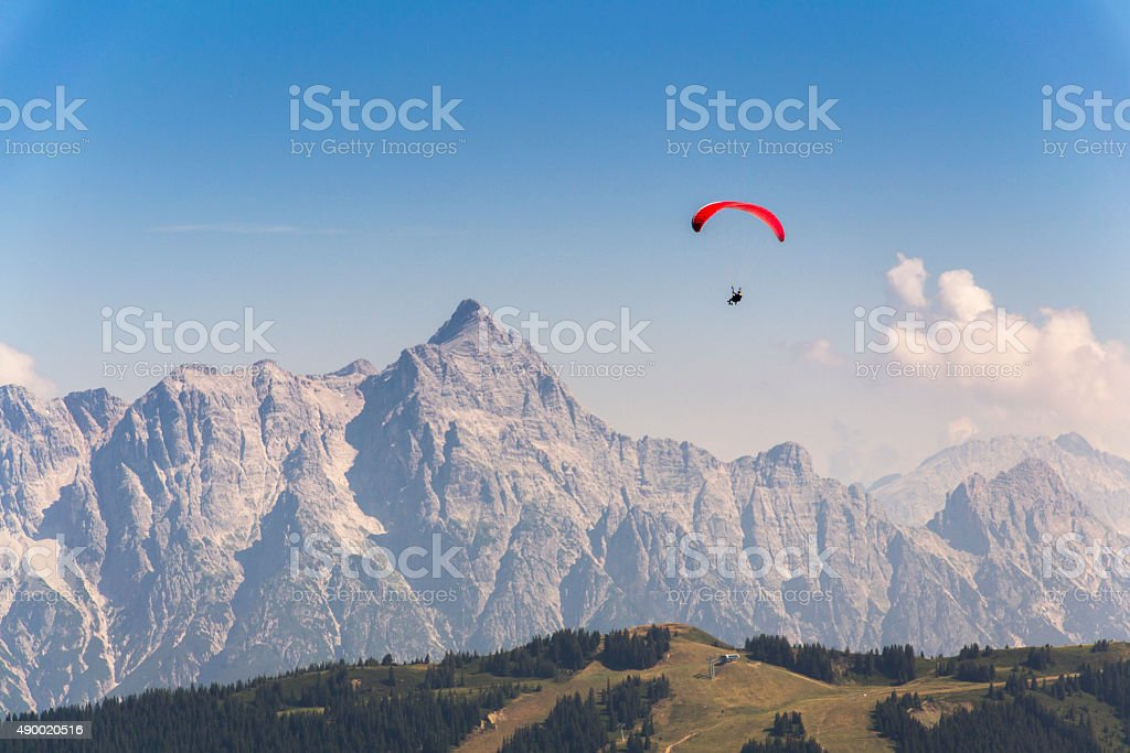 Paraglider flyes over mountains in Alps, Austria stock photo