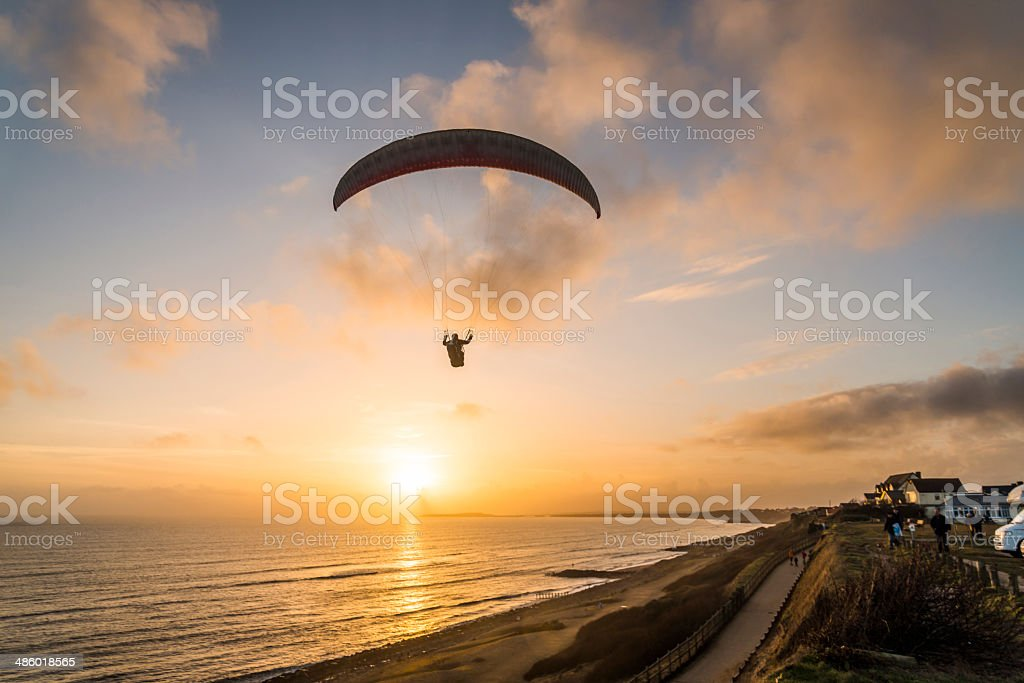 Paraglider flying over beach. stock photo