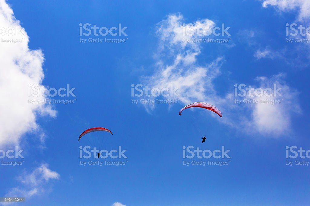 Paraglider flying over clouds stock photo