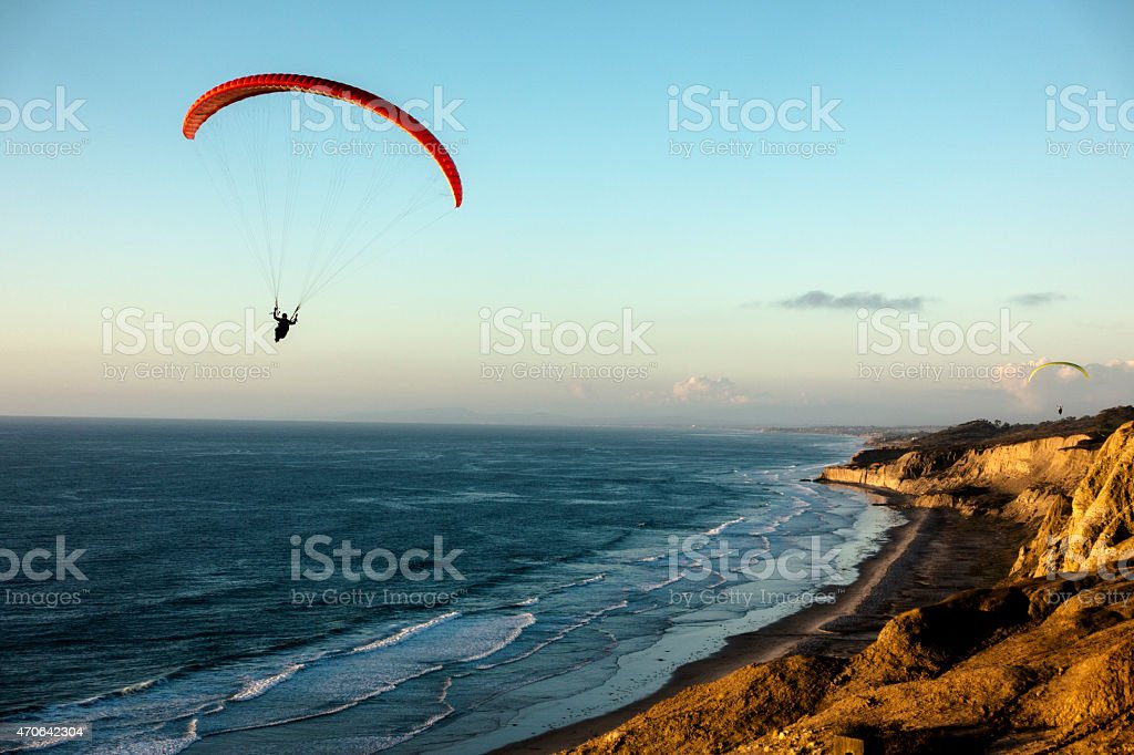 Paraglider flying over ocean cliffs at sunset stock photo