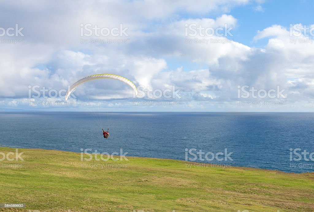Paraglider flying over ocean in summer day stock photo