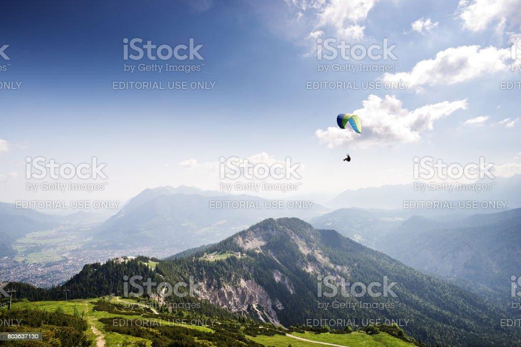 Paraglider gliding across Wetterstein mountain landscape in bavaria stock photo