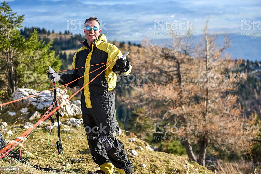Paraglider is checking the ropes and equipement before the fligh stock photo