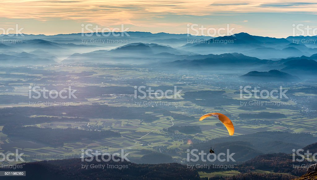Paraglider is flying in the valley stock photo