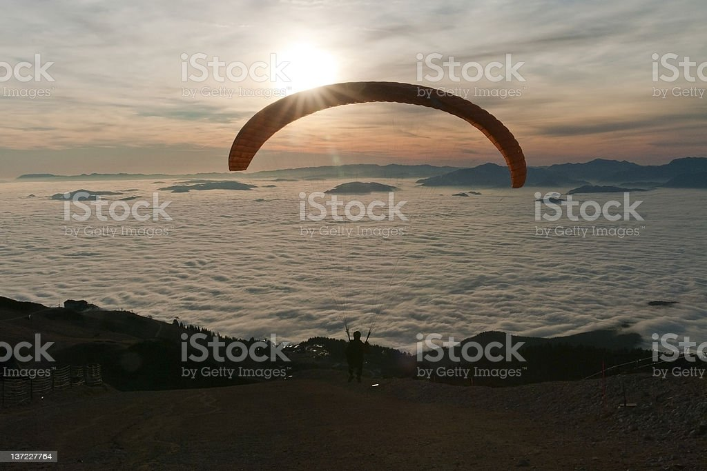 Paraglider is taking off in the sunset royalty-free stock photo