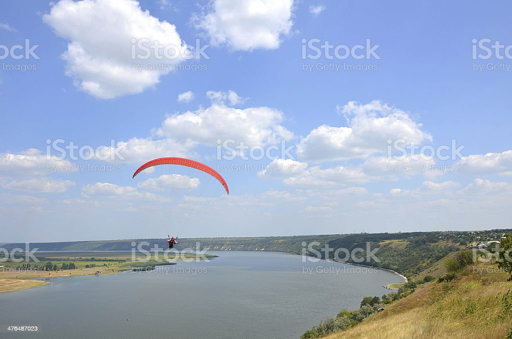 Paraglider jumping over the river stock photo