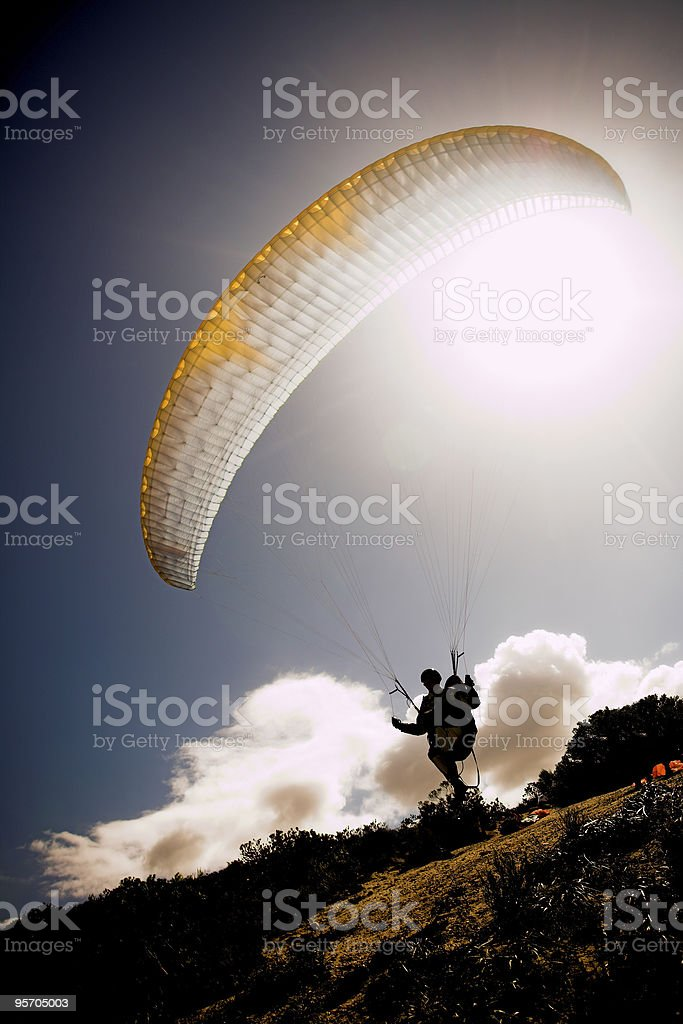 Paraglider launching from the mountain ridge on a clear day stock photo