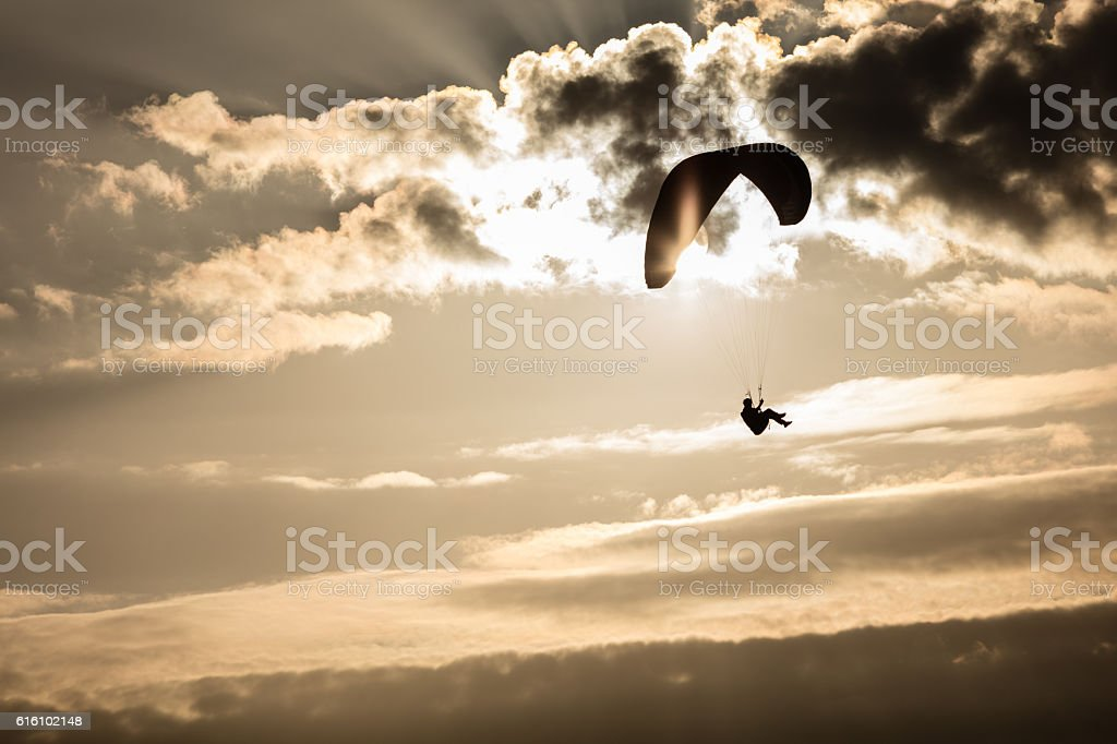 Paraglider lifting up in the evening sun stock photo