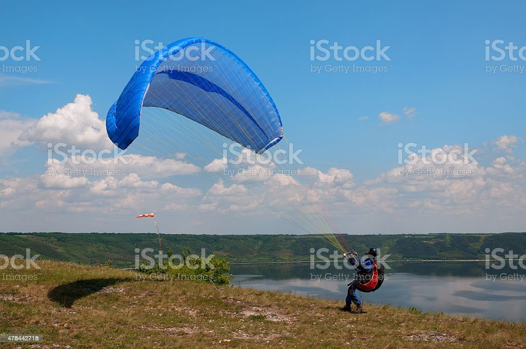 Paraglider prepares to fly over beautiful Bakota reservoir stock photo