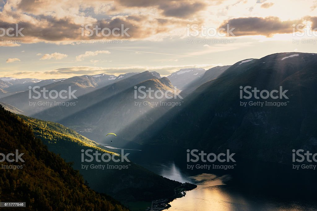 Paraglider silhouette flying over Aurlandfjord, Norway stock photo