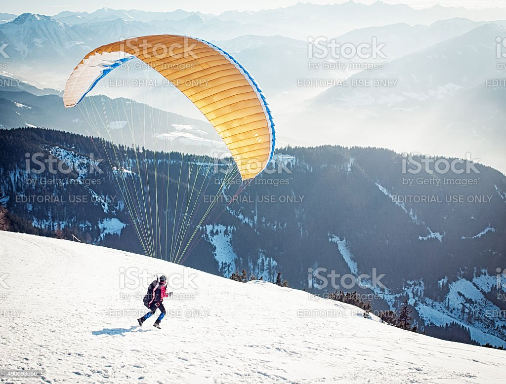 Paraglider Taking Off from Ski Slope stock photo